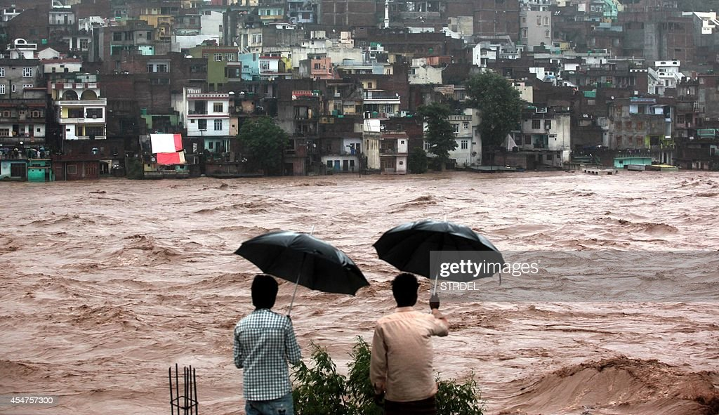 Indian residents look on towards threatened houses as waters from the overflowing Tawi river rage past in Jammu on September 6 2014 Incessant rains...