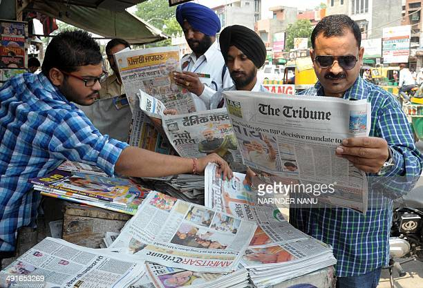 Indian residents pose for a photograph as they read newspapers displaying headlines of the election victory of the Chief Minister of the western...