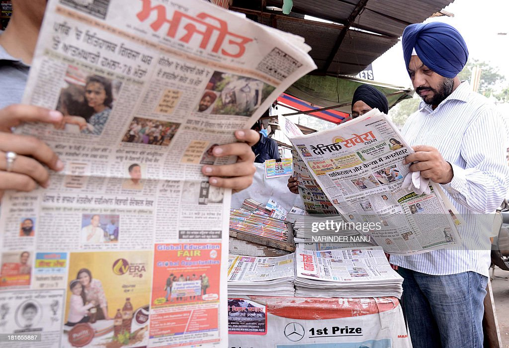 Indian residents read newspapers, displaying front page headlines of attacks on Christians in Pakistan, at a roadside stall in Amritsar on September 23, 2013. The death toll from a double suicide bombing on a church in Pakistan rose to 81, as Christians protested across the country to demand better protection for their community. The attack on All Saints church in the northwestern city of Peshawar after a service on September 22, which has been claimed by the Pakistani Taliban, is believed to be the deadliest ever to target Pakistan's small Christian minority. AFP PHOTO/NARINDER NANU