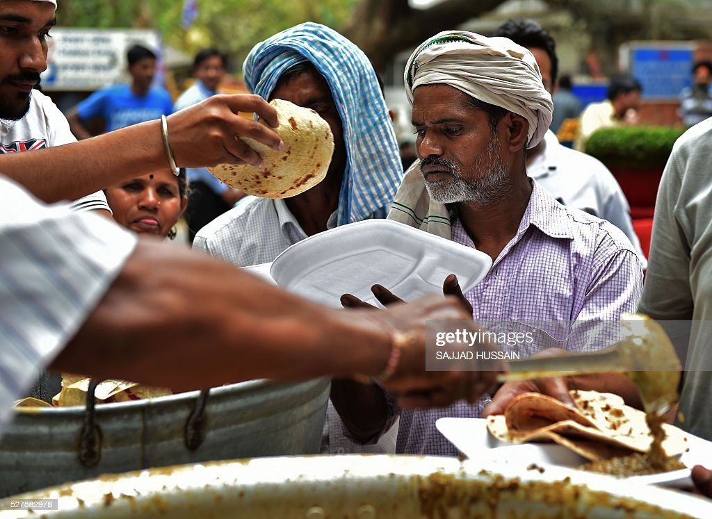 Indian residents receive free food donated by a community kitchen on a hot afternoon in New Delhi on May 3, 2016. / AFP / SAJJAD