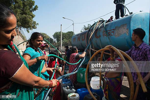 Indian residents remove hoses from a water distribution truck at a distribution point in the lowincome eastern New Delhi neighborhood of Sanjay camp...