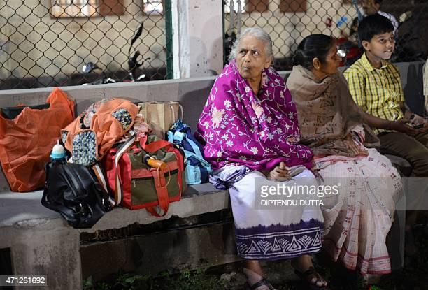 Indian residents rests at a roadside divider in Siliguri on April 26 2015 after a 78 magnitude earthquake hit the region on April 25 in Nepal...