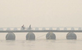 Indian residents ride bicycles as they cross a pontoon bridge during a foggy day in Allahabad on December 23 2013 Northern India continues to face...
