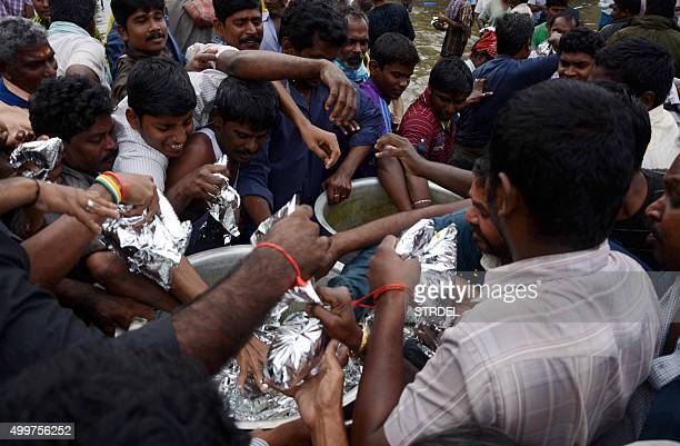 Indian residents scramble for food packages which are being distributed in Chennai on December 3 after flooding hit the southern Indian city follwing...