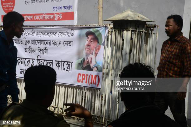 TOPSHOT Indian residents sit near a banner displaying the image of former Cuban president Fidel Castro in Siliguri on November 27 2016 Cuba's...