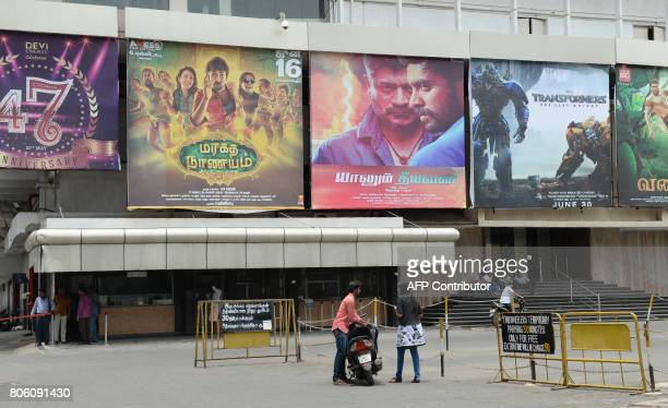 Indian residents stand in front of a closed cinema amid a shutdown called to protest the implementation of the Goods and Services Tax in Chennai on...