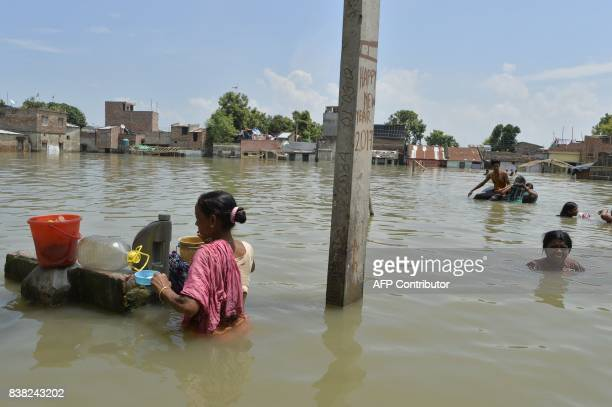 Indian residents swim and wade through flood waters in Malda in the Indian state of West Bengal on August 24 2017 The death toll from floods sweeping...