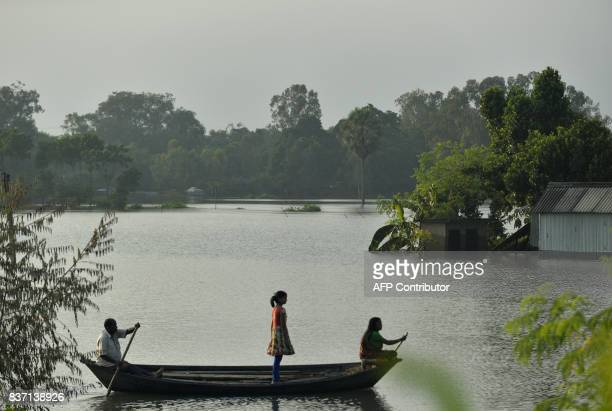 Indian residents travel on a boat near partially submerged houses by flood waters in Gazole village at Malda district in the Indian state of West...