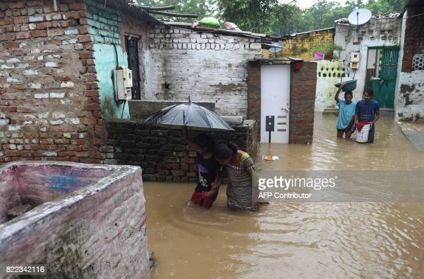 TOPSHOT Indian residents wade through flood waters in a lowlying area near the Sabarmati River in Ahmedabad on July 25 2017 Indian Prime Minister...