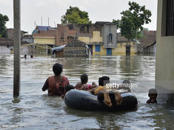 Indian residents wade through flood waters in Malda in the Indian state of West Bengal on August 24 2017 The death toll from floods sweeping South...