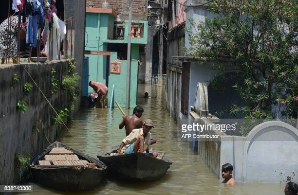 Indian residents wade travel through flood waters in Malda in the Indian state of West Bengal on August 24 2017 The death toll from floods sweeping...