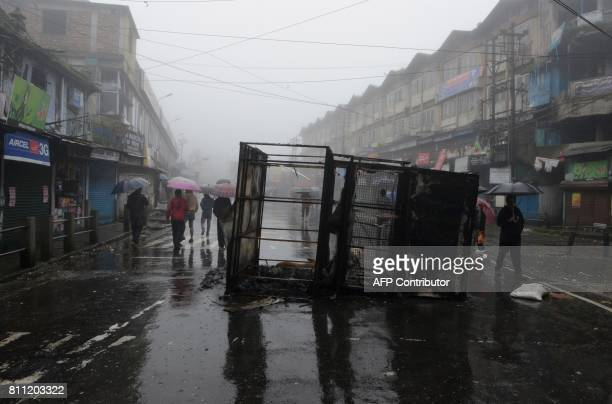 Indian residents walk along a street near a burnt police booth after the July 8 clashes between Gorkhaland supporters and the police during and...