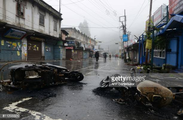 Indian residents walk along a street near a burnt vehicles after the July 8 clashes between Gorkhaland supporters and the police during and...