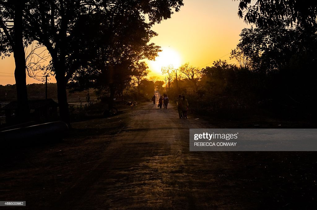 Indian residents walk along the Rukka Road near the Yuwa School and football centre in Hutup Village some 14 kilometres from Ranchi on March 22 2015...