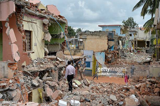 Indian residents walk amidst the debris of demolished houses a day after Bangalore's municipal authority Bruhat Bengaluru Mahanagara Palike brought...