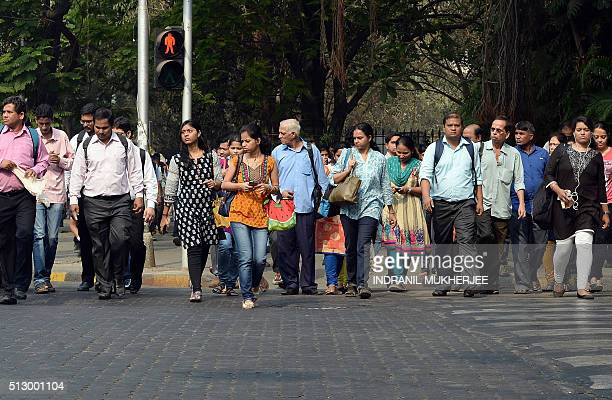 Indian residents walk at a pedestrian crossing in Mumbai on February 29 2016 India pledged to spend $52 billion dollars to double the income of...