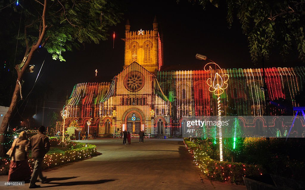 Indian residents walk in front of the All Saints Cathedral decorated with Christmas lights ahead of Christmas celebrations in Allahabad on December...