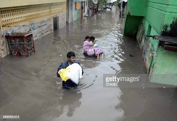 Indian residents walk through floodwaters in Chennai on December 2 2015 India has deployed troops to Tamil Nadu and closed the main airport there...