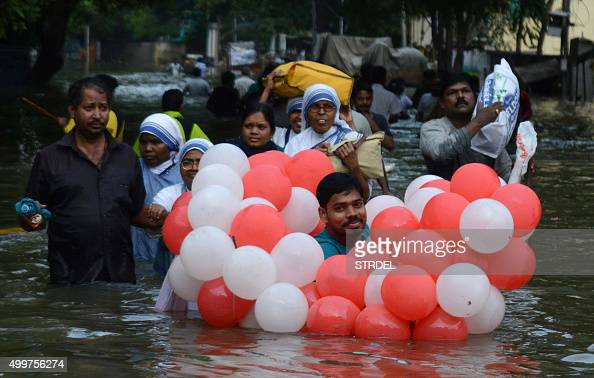 TOPSHOT Indian residents walk through floodwaters in Chennai on December 3 2015 Thousands of rescuers raced to evacuate residents from deadly...