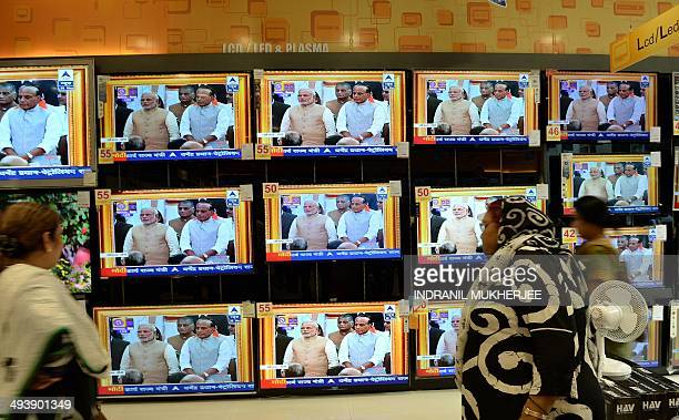 Indian residents watch a bank of televisions featuring images of Narendra Modi taking his oath as India's Prime Minister in New Delhi at a multi...
