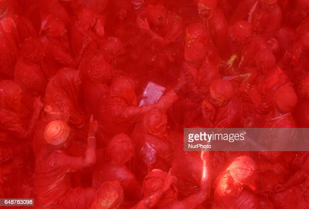 Indian reveler covered in coloured powder perform rituals inside a temple during the Lathmar Holi celebrations in the village of Barsana on March 6...