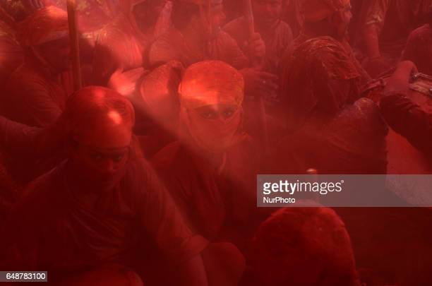 Indian reveler covered in coloured powder sits inside a temple as he and other prays during the Lathmar Holi celebrations in the village of Barsana...