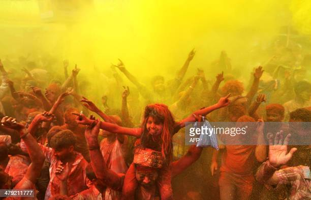 Indian revellers cover each other with coloured powder and dance while taking part in Holi festival celebrations in Guwahati on March 17 2014 Holi...