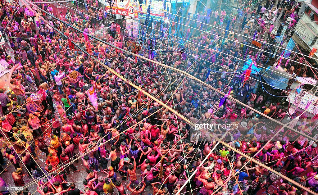 Indian revellers dance on the street during continuing Holi festival celebrations in Allahabad on March 28, 2013. 'Holi', the Festival of Colours, is a popular Hindu spring festival observed in India and Nepal at the end of winter season on the last full moon day of the lunar month.