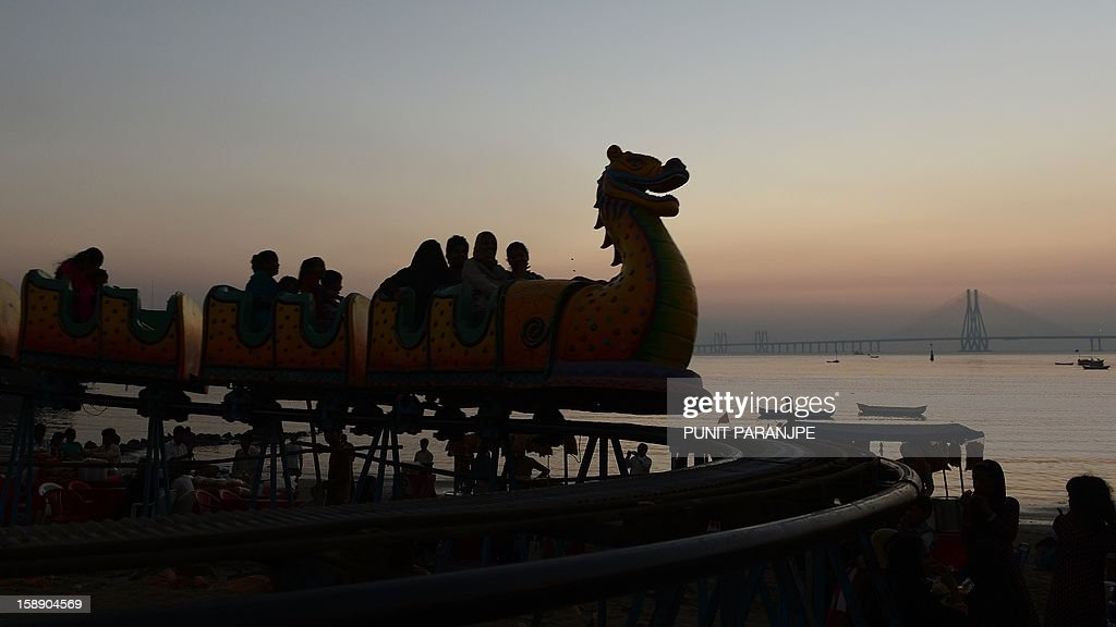 Indian revellers enjoy an amusement park ride during an annual fair in Mumbai on January 3, 2013. The ten day-long fair is being held in honour of the Sufi saint Makhdoom Ali Mahimi on the dusty Mahim beach, which is full of people on giant wheels, toy trains and enjoying gravity-defying stunts in the 'Maut Ka Kuan' or 'Valley of Death'. AFP PHOTO/ PUNIT PARANJPE