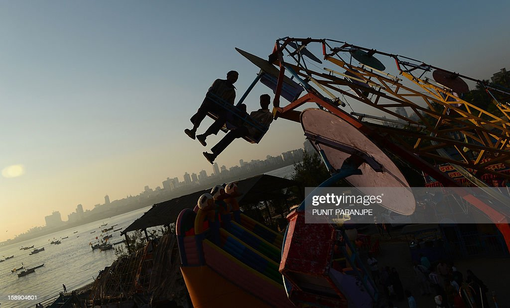 Indian revellers enjoy an amusement park ride during an annual fair in Mumbai on January 3, 2013. The ten day-long fair is being held in honour of the Sufi saint Makhdoom Ali Mahimi on the dusty Mahim beach, which is full of people on giant wheels, toy trains and enjoying gravity-defying stunts in the 'Maut Ka Kuan' or 'Valley of Death'.