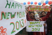 Indian revellers hold placards in Amritsar on December 31 2012 Sydney will kick off a wave of dazzling firework displays welcoming in 2013 from Dubai...