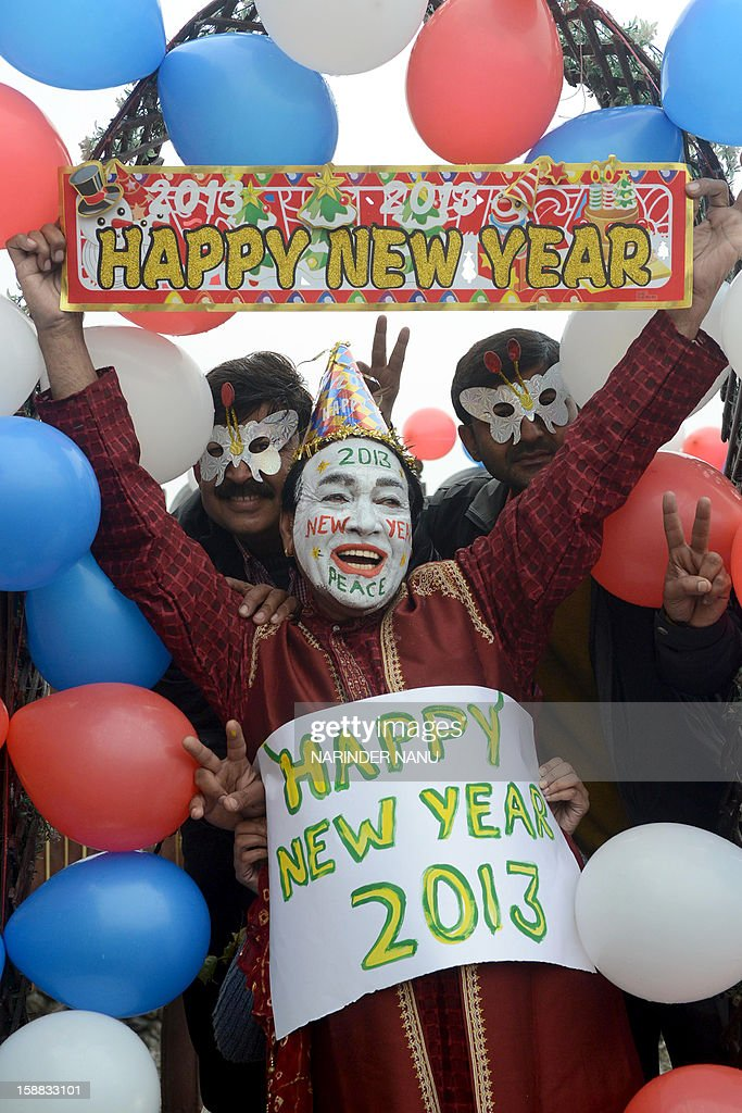 Indian revellers hold placards in Amritsar on December 31, 2012. Sydney will kick off a wave of dazzling firework displays welcoming in 2013, from Dubai to Moscow and London, with long-isolated Yangon joining the global pyrotechnics for the first time.