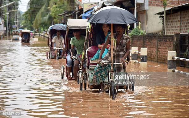 Indian rickshaw pullers transport customers through floodwaters in the Anilnagar area of Guwahati on July 19 2016 Floods in the northern Indian state...