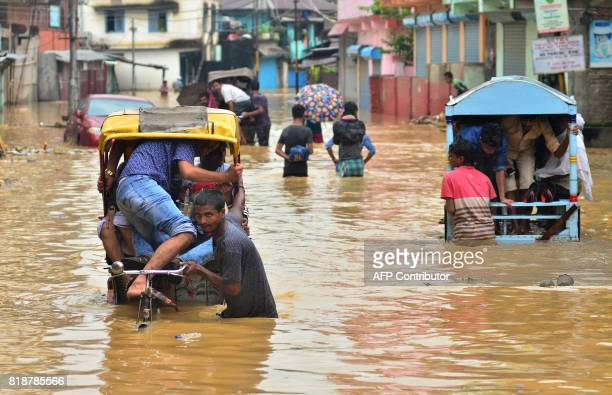 TOPSHOT Indian rickshaw pullers transport people to a higher ground along a flooded street in Dimapur in Nagaland state on July 19 2017 / AFP PHOTO /...