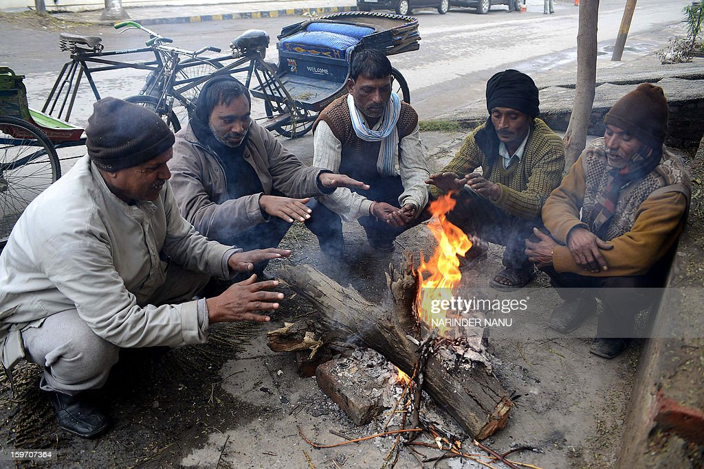 Indian rickshaw pullers warm themselves around a fire in Amritsar on January 19, 2013. The northern Indian city of Amritsar faces severe cold conditions with the temperature dipping towards the zero degree Celsius mark.