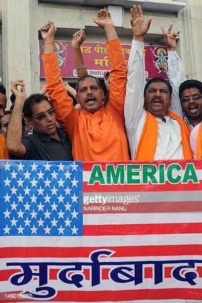 Indian rightwing Hindu party Shiv Sena activists shout slogans before burning a US flag during a protest outside the Goddess Kali temple in Amritsar...