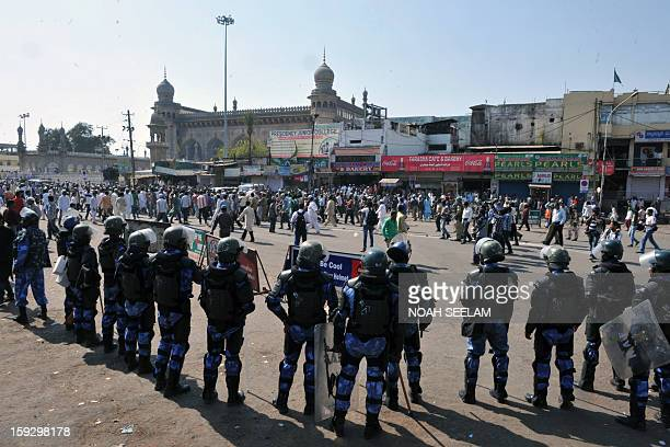 Indian riot police keep watch as supporters of the MajliseIttehadul Muslimeen demonstrate outside the historic Mecca Masjid following congregational...