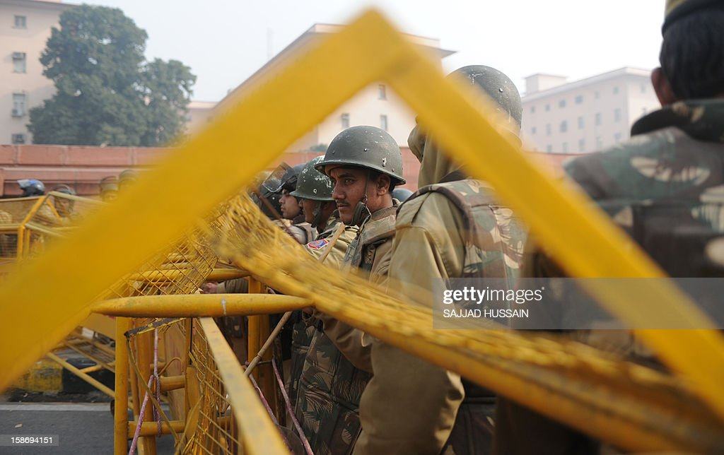Indian riot police look on as they keep watch along a sealed-off road leading towards the landmark India Gate monument following weekend clashes between demonstrators and police in New Delhi on December 24, 2012. Indian Prime Minister Manmohan Singh has appealed for calm and vowed to protect women as police struggled to quell increasing outrage over sex crimes following the gang-rape of a student.