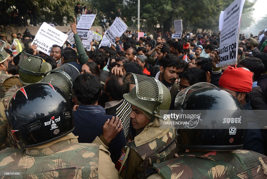 Indian riot policemen stand in front of a demonstrating crowd during a protest calling for better safety for women following the rape of a student in the Indian capital, in New Delhi on December 27, 2012. An Indian student who was left fighting for her life after being brutally gang raped on a bus in New Delhi arrived December 27 in Singapore for treatment at a leading hospital. The attack sparked a wave of protests across India in which a policeman died and more than 100 police and protestors were injured. AFP PHOTO/RAVEENDRAN