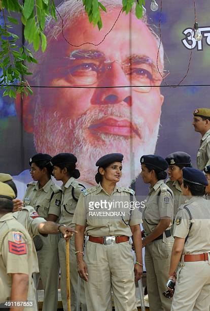 Indian riot policewomen standin front of a billboard of Bharatiya Janata Party 's Narendra Modi in front of the BJP headquarters in New Delhi on May...
