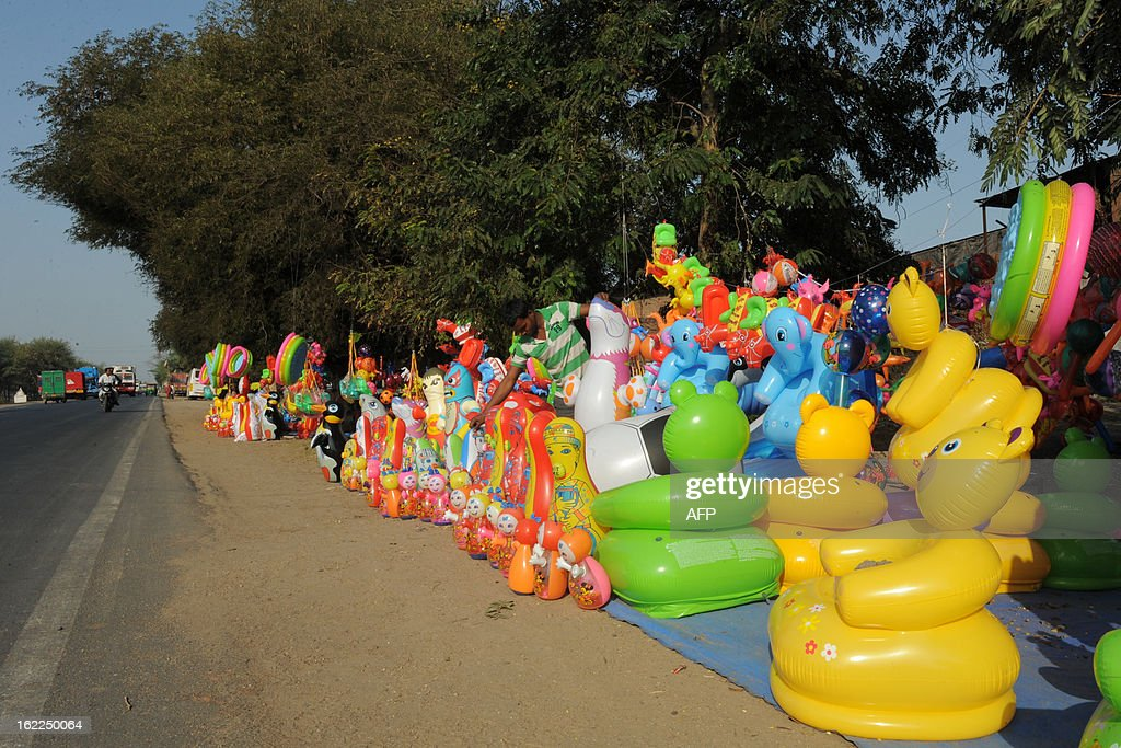Indian roadside toy vendor Rinku Thakur (C, in green striped shirt) arranges a variety of blow-up toys on the outskirts of Ahmedabad on February 21, 2013. India, the world's most populous democracy, is struggling to avert a ratings downgrade of its sovereign debt to junk status due to its worsening finances, with growth expected to be as low as 5.0 percent in the fiscal year to March 2013. AFP PHOTO / Sam PANTHAKY
