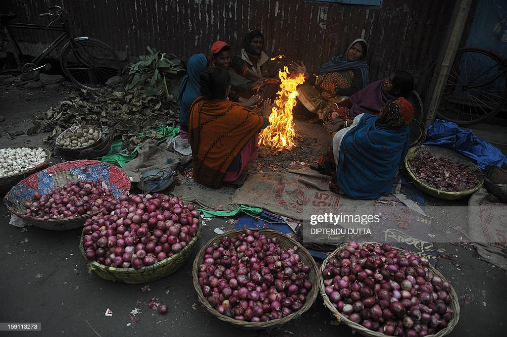 Indian roadside vegetable sellers warm themselves around a bonfire during a foggy and cold day in Siliguri on January 8, 2013. As thousands of homeless people sought places in temporary shelters, the unusual cold in throughout India has been attributed to dense fog which has obscured the sun and disrupted airports and trains, as well as icy winds from the snowy Himalayas to the north. AFP PHOTO/Diptendu DUTTA