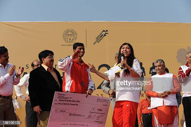 Indian runner Arvindkumar Yadav gestures along with Megha from Radio Mirchi after receiving his winning cheque and trophy for winning the men's...