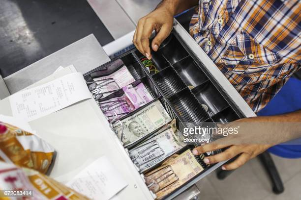 Indian rupee banknotes of various denominations sit in a cash register at at the checkout counter of a Big Bazaar hypermarket operated by Future...