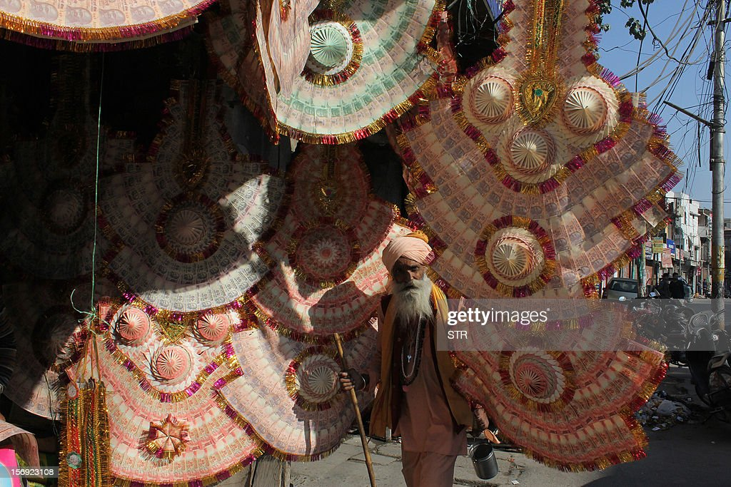 A Indian Sadhu - holy man - walks through currency garlands hanging outside a store in Jammu on November 25, 2012. Currency garlands are used to felicitate individuals at public functions and weddings.