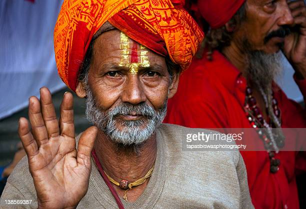 Indian sadhu in colorful attire offering blessing