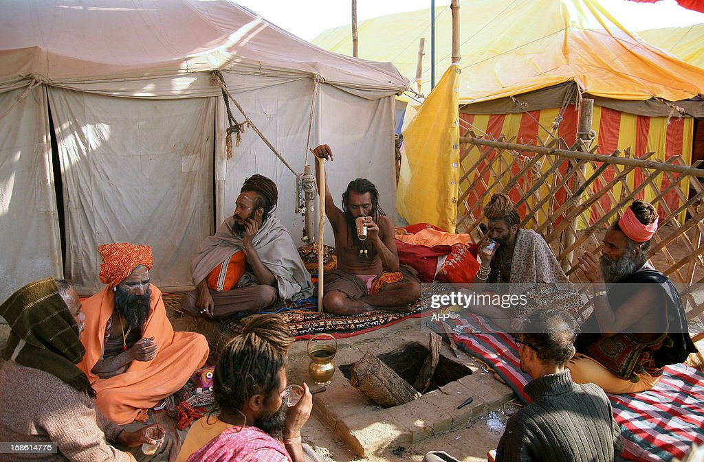 "Indian Sadhu, Mahant Radheypuri Juna Akhara (C), who has held his arm in an upward position for twelve years, sits with fellow Sashus in their camp on the bank of ""Sangam,"" the confluence of the three rivers Ganges, Yamuna and mythical Saraswati in Allahabad on December 21, 2012, ahead of the Mahakumbh Mela. The Kumbh Mela, which is scheduled to take place in the northern Indian city in January and February 2013, is the world's largest gathering of people for a religious purpose and millions of people gather for this auspicious occasion. AFP PHOTO/ Sanjay KANOJIA"
