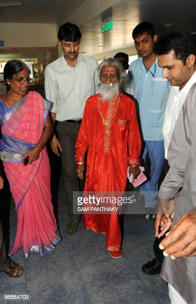Indian sadhu Prahlad Jani is escorted by devotees and relatives after a press conference in Ahmedbad on May 6 2010 A team of military doctors backed...