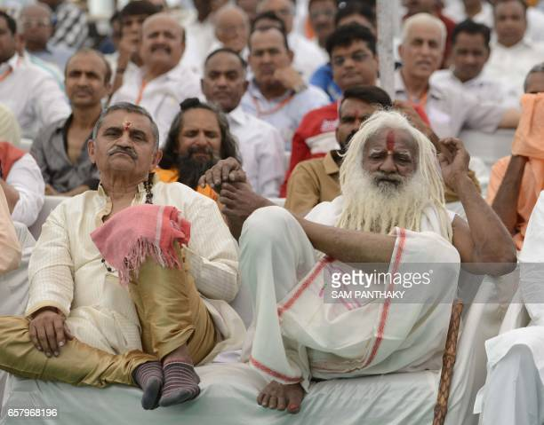 Indian Sadhus and other delegates look on during a gathering of The Vishva Hindu Parishad at The GMDC grounds in Ahmedabad on March 26 which was...