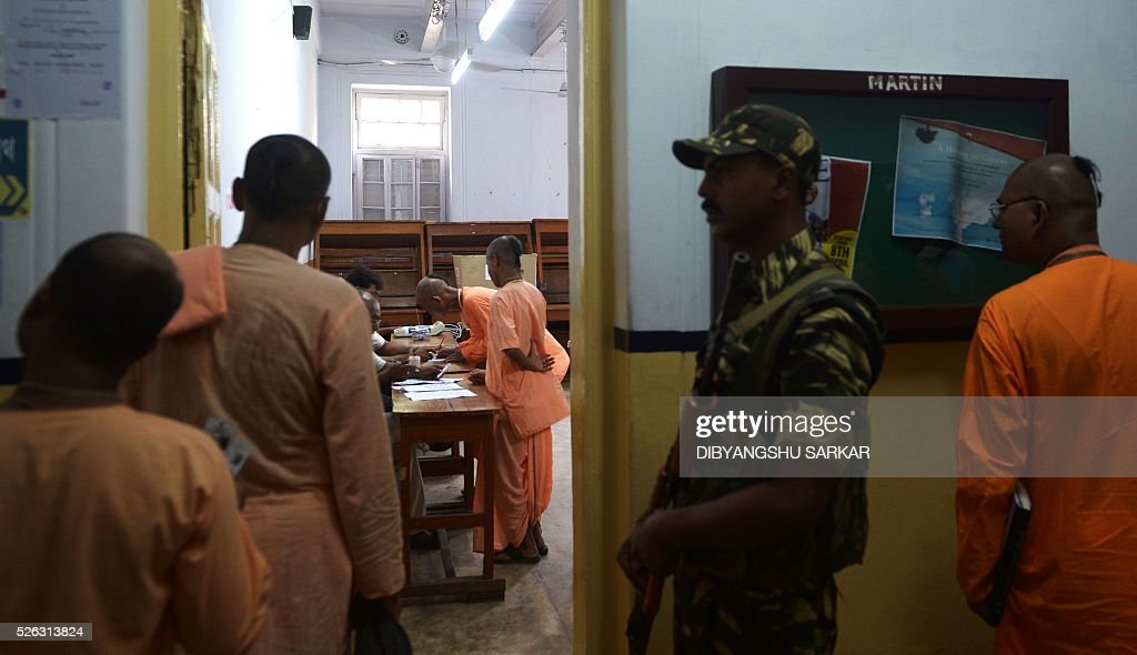 Indian Sadhus are supervised by a paramilitary soldier as they wait to cast their ballots in state assembly elections at a polling station at a polling station in Kolkata on April 30, 2016. State assembly elections in West Bengal are taking place from April 4 to May 5. / AFP / Dibyangshu SARKAR